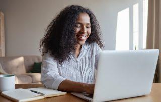 Fotografia colorida de jovem utilizando um laptop e sorrindo. Há um caderno ao lado do computador.
